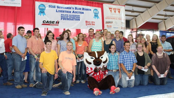 Winners of the Governor's Blue Ribbon Sale of Champions Foundation Scholarships are joined by scholarship sponsors, Bucky Badger and Gov. Scott Walker (last row with cowboy hat) prior to the Governor's Blue Ribbon Livestock Auction on Aug. 10 at the Wisconsin State Fair.