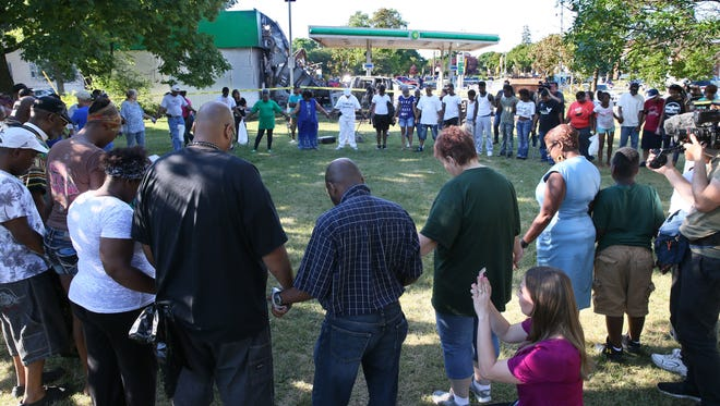 Residents pray for peace next to the burned out BP gas station at 3114 N. Sherman Blvd.