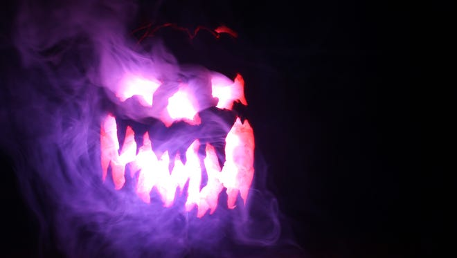 A carved pumpkin breathing fog illuminated by an LED light.