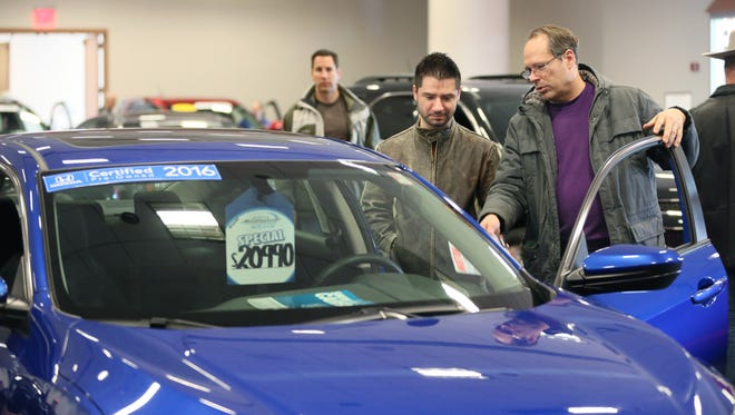 Keith Krueger of Pewaukee (right) and his son Christopher Krueger of Waukesha (left), look over a certified pre-owned 2016 Honda Civic EX-T with 6,000 miles on it for sale at the show in the used car area.