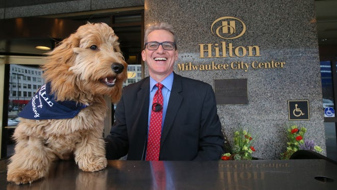 "Millie, the ""canine concierge"" at Hilton Milwaukee City Center, greets guests at the hotel with her owner, Rusty Dahler, the hotel's concierge."