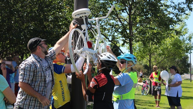 People lock a ghost bike to a light pole on N. Taft Avenue nears its intersection with 50th Street in Loveland, where Loveland cyclist George Nelson died in a crash last week. The bike is used as a memorial and a reminder to drive and cycle safely.