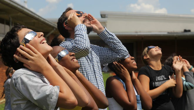 Sixth grade teacher Joshua Swint and his class watch the eclipse at Cobb Middle School Monday.