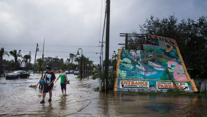 Pedestrians walk past the iconic Everglades Wonder Gardens sign, damaged by Hurricane Irma, in downtown Bonita Springs on Monday, Sept. 11, 2017.