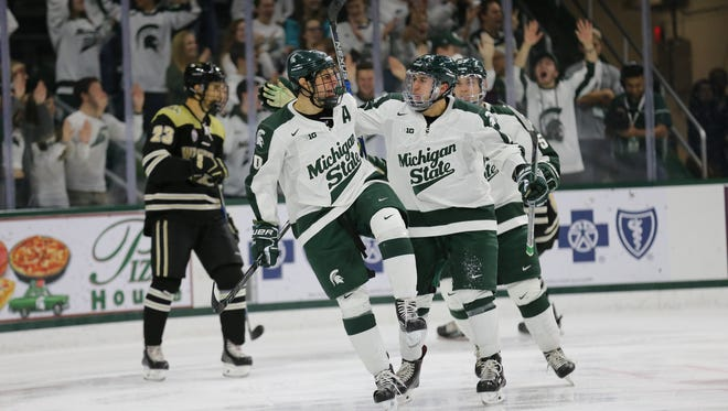Michigan State celebrates a game-clinching empty-net goal from Sam Saliba, left, in the final minute of Friday night's 6-4 win over Western Michigan at Munn Ice Arena.