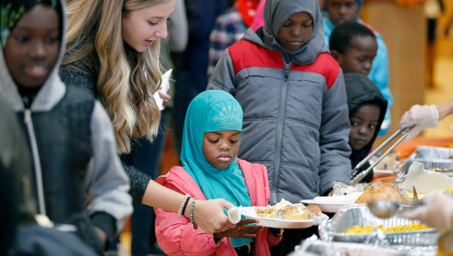 Teacher Jenna Treahy helps Dahiro Hassn, 7, of Rochester get her meal during An American Celebration Thanksgiving Dinner at the Rochester International Academy. This was the seventh annual Thanksgiving celebration for the school's students, families, and community partners.
