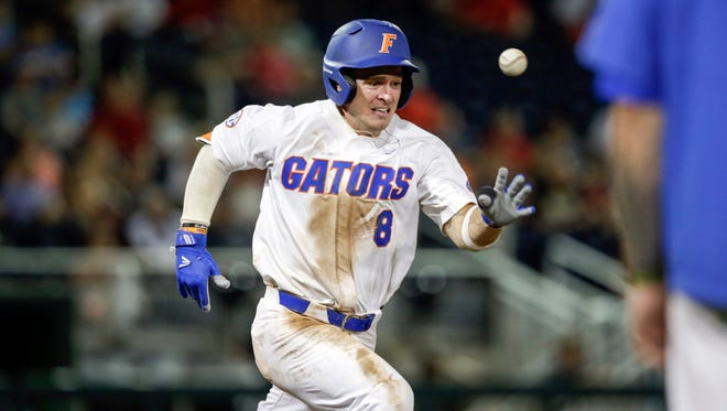 Florida's Deacon Liput races to first base but is out on the throw in the ninth inning of an NCAA College World Series baseball game against Texas Tech.