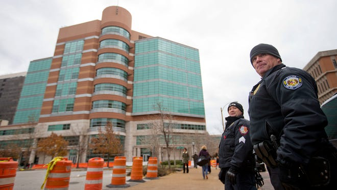 Police officers stand outside the Buzz Westfall Justice Center where a grand jury is convening to consider possible charges against the police officer who fatally shot Michael Brown in nearby Ferguson, Monday, Nov. 24, 2014, in Clayton, Mo.