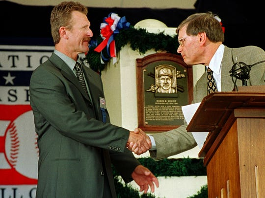 Baseball Commissioner Bud Selig shakes Robin Younts hand as he comes to the podium for his induction speech July 24, 1999. The Hall of Fame plaque is between them.
