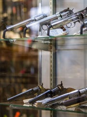 Guns sit behind a glass case at the Cedar Post Pawn Shop, Tuesday, Jan. 5, 2016.