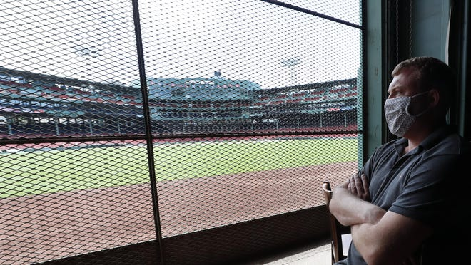 Joe Hicks, Bleacher Bar director of operations, looks out at Fenway Park from the bar in Boston. If Major League Baseball's plans remain on schedule, it may be one of the few places fans will be able to watch a Red Sox game in person this season.
