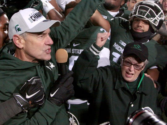 Michigan State football coach Mark Dantonio, left, and university president Lou Anna K. Simon celebrate their Big Ten East Division championship in November 2015 in East Lansing.