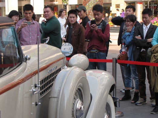People photograph classic cars at the Wangfujing shopping district on Oct. 11 in Beijing. The display is promoting the annual Classic Cars Challenge, a race which will begin at the Great Wall and will finish Friday in Shanghai.