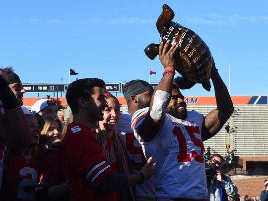 Ohio State tailback Ezekiel Elliott holds up the Illibuck, the wooden turtle that goes to the winner when OSU and Illinois meet on the football field.