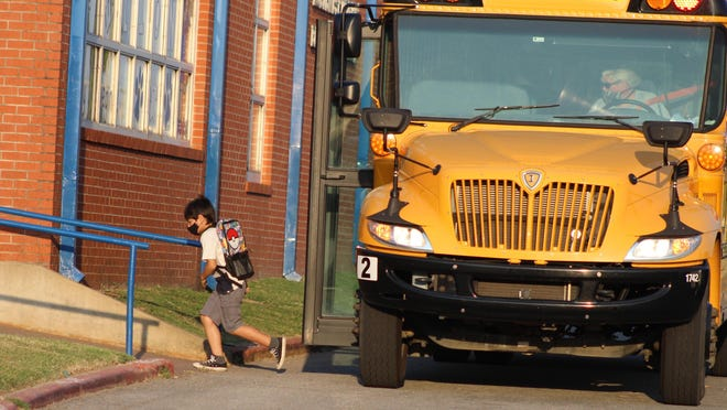 A Durant ISD student exits a school bus and heads toward the building at Northwest Heights Elementary School on Aug. 24, which was the first day of classes for the fall semester.