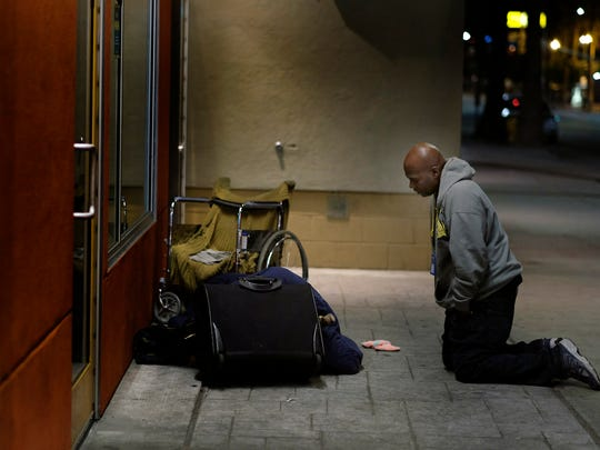 Anthony Ruffin, 48, kneels to speak with a homeless man as he sleeps on the sidewalk in Hollywood, Calif.