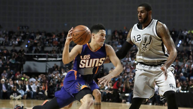 Phoenix Suns Devin Booker, left, drives the ball as San Antonio Spurs LaMarcus Aldridge attempts to block him, in the first half of their regular-season NBA basketball game in Mexico City, Saturday, Jan. 14, 2017.