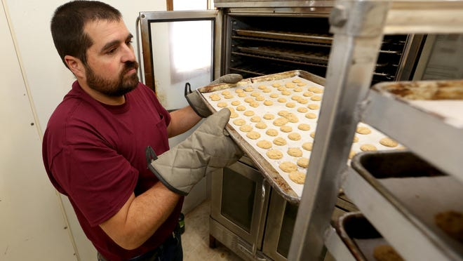 Abner Schmucker lifts hot trays of freshly baked peppernuts out of the ovens to cool on racks Tuesday morning at his family-owned business, Helmuth Bakery. Abner and his wife, Angela, have owned the business for eight years.