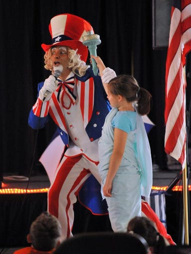 Mark Abbati holds Hannah Hansen's arm in the air after dressing the eight-year-old Lancaster resident as the Statue of Liberty July 22, 2014, at River Valley Mall in Lancaster. Abbati brought his U.S. History Fun Show to the Lancaster Festival as part of the children's entertainment portion.