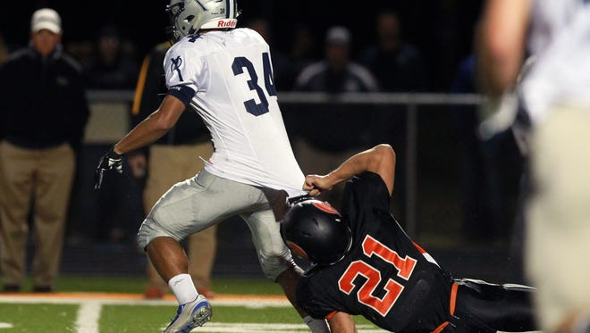 Solon's Trevor Nelson tackles Cedar Rapids Xavier's Maliki Wilson during their game at Solon on Friday, Sept. 11, 2015.