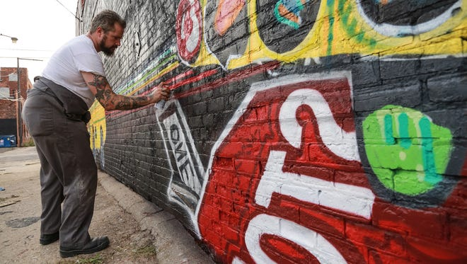 Artist Ryan C. Doyle works on a mural near Orleans and Division during the Murals in the Market festival on Friday September 18, 2015 at the Eastern Market in Detroit. About 40 artists are on hand creating street art through the week.