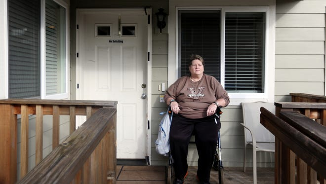 Holly Schmitz sits on the porch of the adult foster care home she has lived at since August, but which she will have to move out of by Monday, Feb. 1. Schmitz was given a thirty day notice to leave after her provider was notified they would be facing steep rate cuts in assistance dollars.