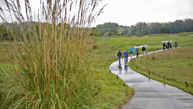 Golfers and fans walk the winding cart path on a rainy day one of the 44th Annual IHSAA Girls Golf State Finals, at Prairie View Golf Club in Carmel, Friday, September 30, 2016.