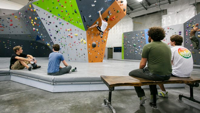 South Salem High School student Caleb Laws, 18, ascends a wall at Rock Boxx as friends watch from the mats and benches. A student day pass is $10; an adult day pass costs $13.
