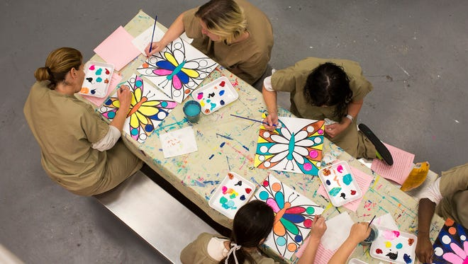 """Inmates in the recovery pod of the Hamilton County Justice Center participate in a weekly art and spirituality program led by Sarah Hellmann, executive director of Art For All People. Hellmann said, """"I remind them they are indeed good. I help them rise above their current struggle."""" She added, """"None of this would be possible if it wasn't for Maj. McGuffey's commitment to the rehabilitation of these inmates."""""""