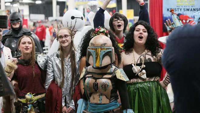 Attendees cheer for a television station while dressed during the Motor City Comic Con at the Suburban Collection Showcase in Novi on Friday, May 19, 2017.