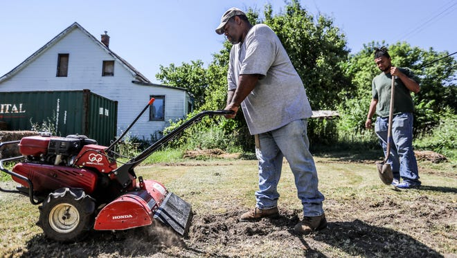 Mark Covington, 46, started the Georgia Street Community Collective with his family in his childhood neighborhood where his mother lives in 2008 after being out of work and cleaning up empty lots nearby. Covington tills the land on an empty plot near GSCC to plant garlic with his son, Andre Covington, 22, in Detroit on Friday, July 6, 2018.