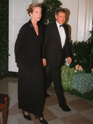 """FILE - In this Feb. 5, 1998 file photo, Harrison Ford and his wife Melissa Mathison arrive at the White House for an official dinner for the British Prime Minister hosted by President Clinton in Washington. Mathison, the screenwriter who crafted the enchanting worlds of iconic family films including """"E.T. the Extra Terrestrial,"""" has died. She passed away Wednesday, Nov. 4, 2015, at age 65 after a bout with neuroendocrine cancer, her sister, Melinda Mathison Johnson, confirmed.  Mathison was married to Harrison Ford for 21 years and divorced in 2004. (AP Photo/Neshan H. Naltchayan, File)"""