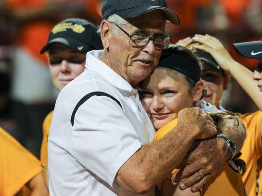 Crescent head coach Gary Adams, left, hugs senior pitcher