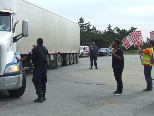 Security guards escort a trucker into the Arbor Hills