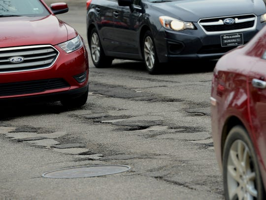 Cars attempt to dodge potholes on Michigan Avenue in Lansing on Tuesday, April 26, 2016,