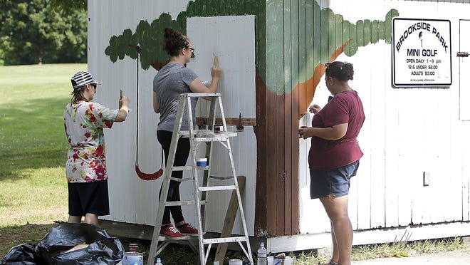 Amanda Kencescan, Tanner Eitman and GiGi Klopzek-Obringer work on painting a mural on the office shed at the Brookside Miniature Golf Course in Ashland as the renovations continued Monday on the course. It was hoped the features on the holes would be placed on Monday, and the course would open on Friday, but the project hit a delay when the glue that was being used to adhere the carpet to the concrete was recalled. Once that issue is taken care of, the project can move forward.