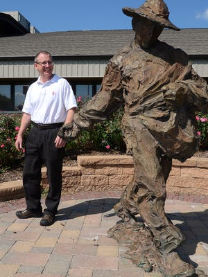 Highland United Methodist Church's new Reverend Tom Anderson walks around a sculpture of The Sower outside the Livingston Road location.