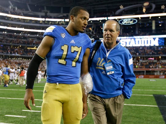 UCLA quarterback Brett Hundley (17) and Rip Scherer, right, walk off the field after a game against Texas, Saturday, Sept. 13, 2014, in Arlington, Texas.