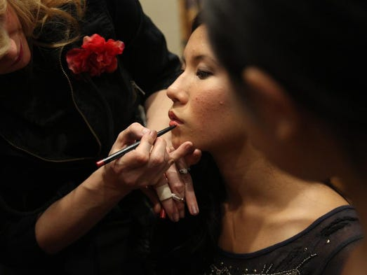 A model gets her makeup done by W Salon makeup artists before walking down the runway in the Friday night show of Fashion Week. The runway was set up down the center aisle of Third Presbyterian Church on Meigs Street and guests filled the pews and balcony areas.