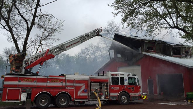 Crews use a ladder truck on a barn fire on 464th Avenue south of Colton on Thursday.