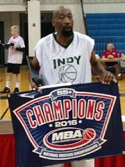James Adams of Indy All-Stars holds the national championship banner for the 55 and older division at the Masters Basketball Association tournament in Florida.