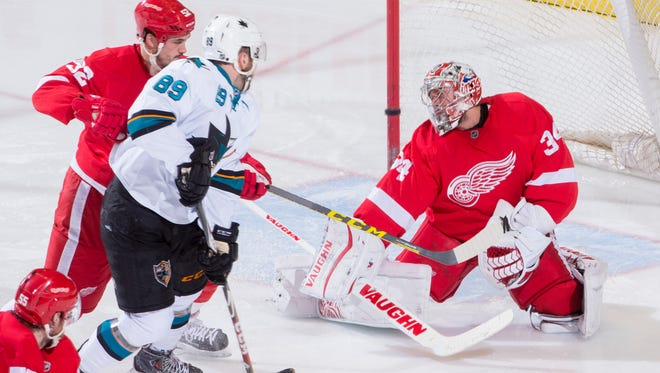 San Jose left wing Barclay Goodrow watches as a shot by teammate Logan Couture (not pictured) flies past Detroit's Jonathan Ericsson, left, and goalie Petr Mrazek for a third-period goal.
