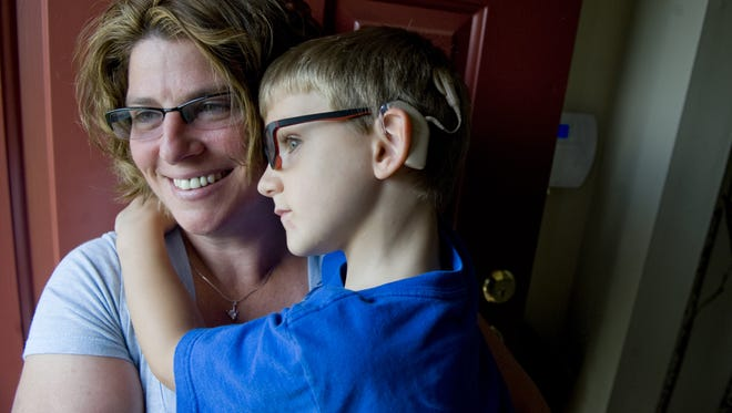 Kim Norton holds her 5-year-old son Henry in their Mount Laurel home in July 2013.  Henry was born deaf and is now going blind from a rare genetic disease called Usher syndrome.