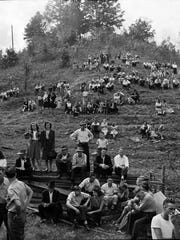 Spectators watched from a hillside while Rev. Oscar Hutton lead a revival that included the handling of venomous snakes, near the Kentucky-Virginia border.  Oct 26 1947