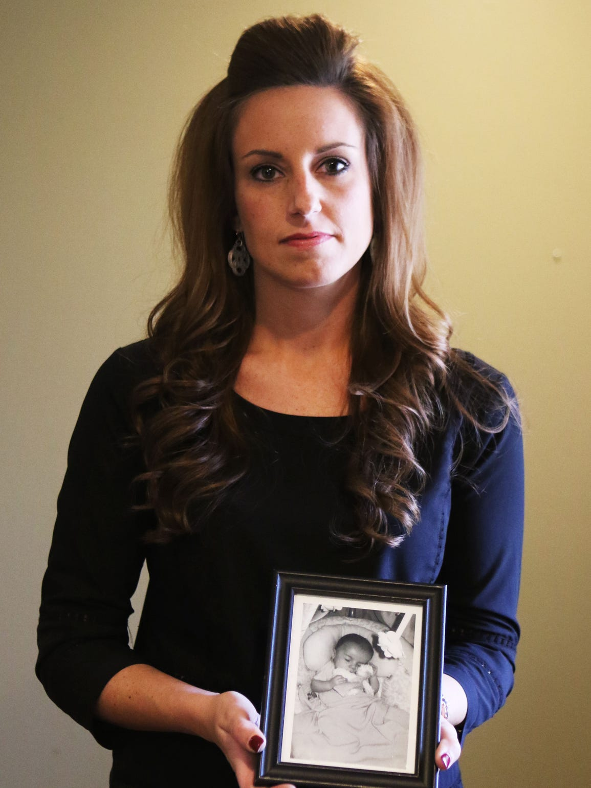 Audra Mahoney holds a photo of her son Maddox on Tuesday,