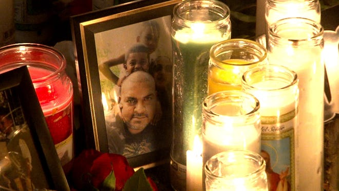 """A photo of Lyndon """"Shane"""" Beharry, his common-law wife Amanda Morris, and their two children, 7-year-old Brandon and 4-year-old Brian, sits among candles last Wednesday evening outside their Joline Avenue home in Long Branch."""