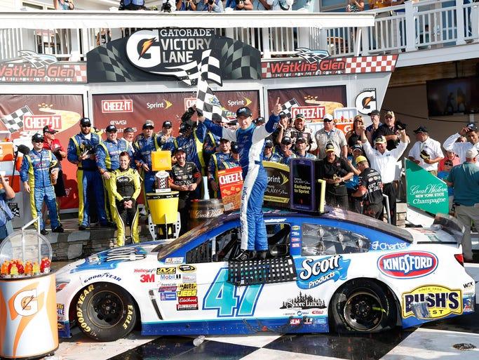Aug 10, 2014; Watkins Glen, NY, USA; NASCAR Sprint Cup Series driver AJ Allmendinger (47) celebrates in victory lane after winning the Cheez-It 355 at Watkins Glen International. Mandatory Credit: Kevin Hoffman-USA TODAY Sports