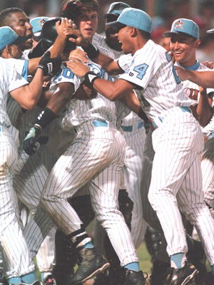"""The Erie SeaWolves celebrate with Jose Guillen, center, after he hit the game-winning home run in the first game at what is now known as UPMC Park on June 20, 1995. The SeaWolves beat the Jamestown Jammers 3-2 at what was then known as """"the downtown ballpark"""" and would later be named Jerry Uht Park."""