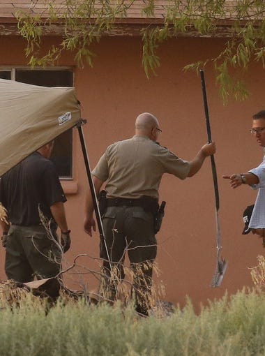 Pinal sheriff's deputies and investigators dig behind a home along West Papago Road Wednesday, July 1, 2015  in Maricopa, Ariz.