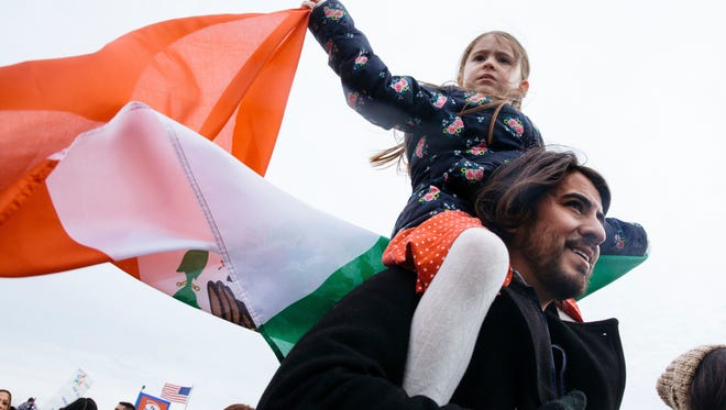 """Eva Marquez, 6, waves the flag of Mexico while riding on her father Marco's shoulders during a protest for a +Day Without Immigrants"""" protest Thursday, Feb. 16, 2017, in St. Paul, Minn. It was part of a nationwide rally designed to show how important immigrants are to daily life."""